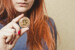 Red-haired girl holds bitcoin gold coin in her hand